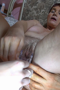 Short haired granny is inserting in her pussy every toys she had and young lesbian is helping her
